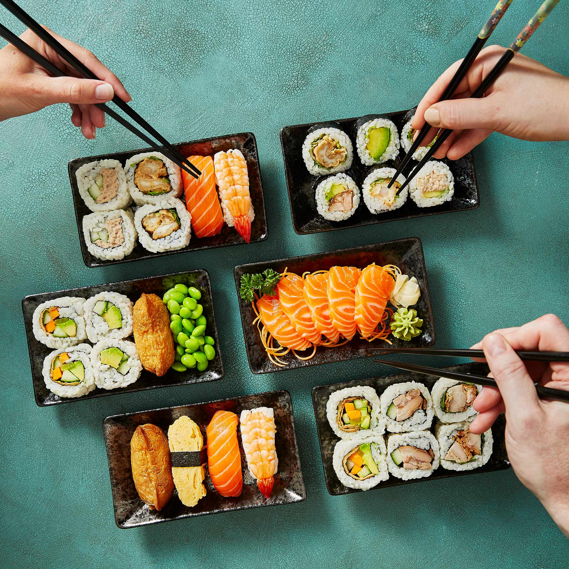People reaching for SushiSushi MiniPack with chopsticks