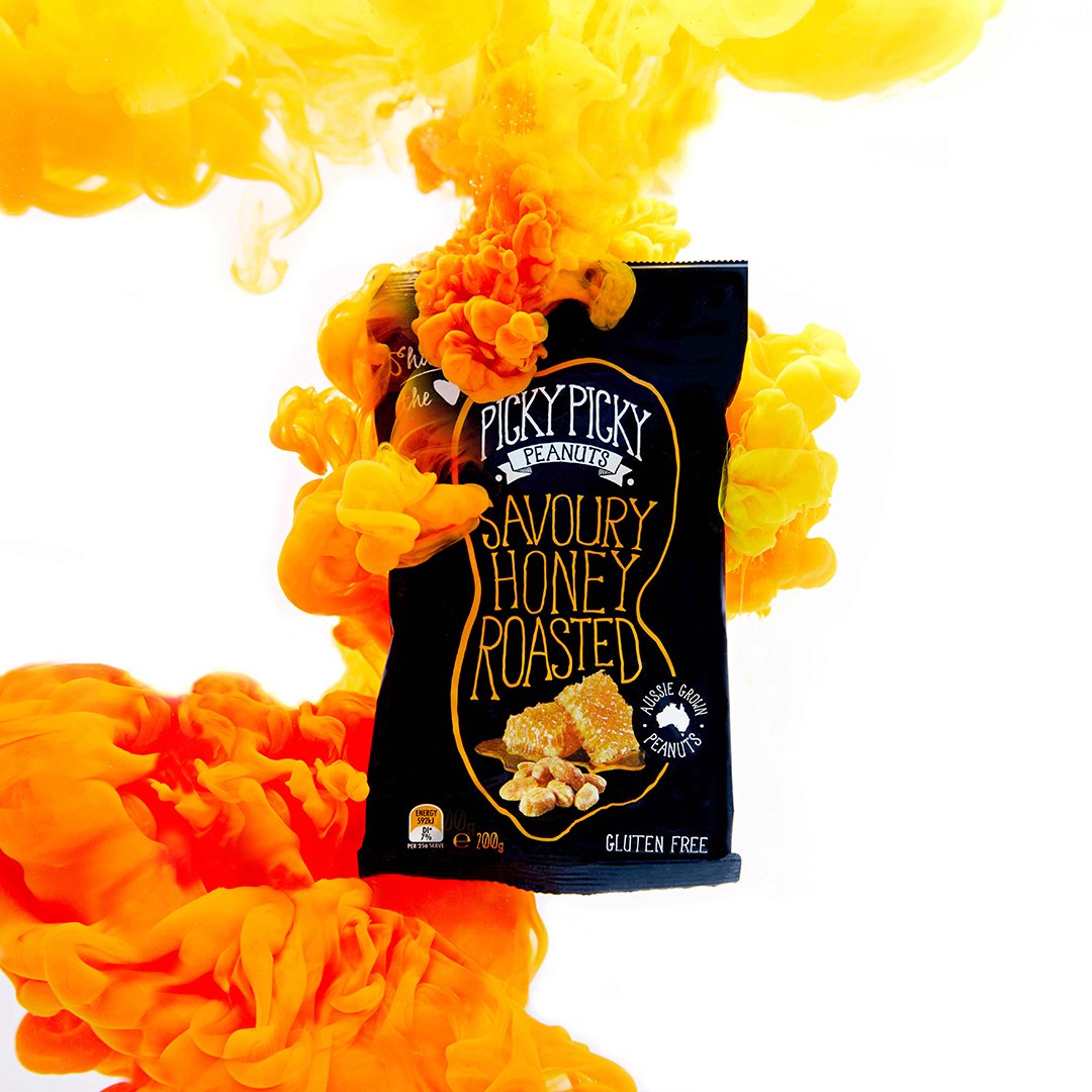 Picky-Picky Honey Roasted Peanuts pack creatively photographed siting in a orange and yellow cloud