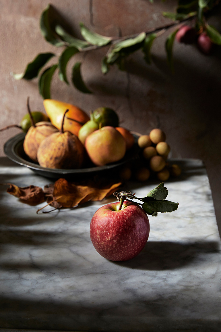 a apple with a leaf on stem sitting a Marble bench with a bowl of fruit behind with beautiful light