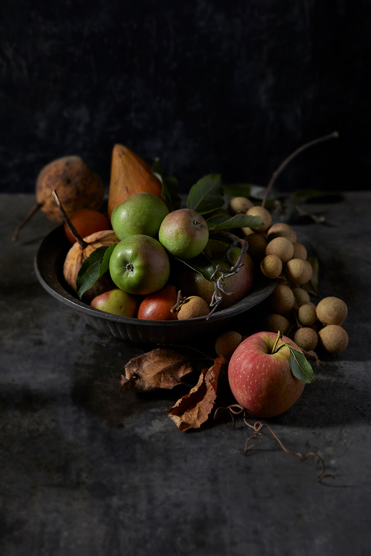 A Romantic dark and moody image of a bowl of unusual fruit with apples
