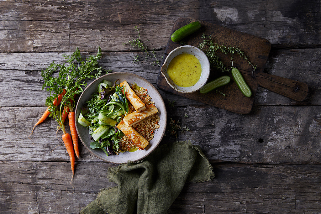 An ancient Grain salad Bowl with Cucumber Ribbons on a rustic timber background food styled with a green napkin and timber cutting board loose carrots