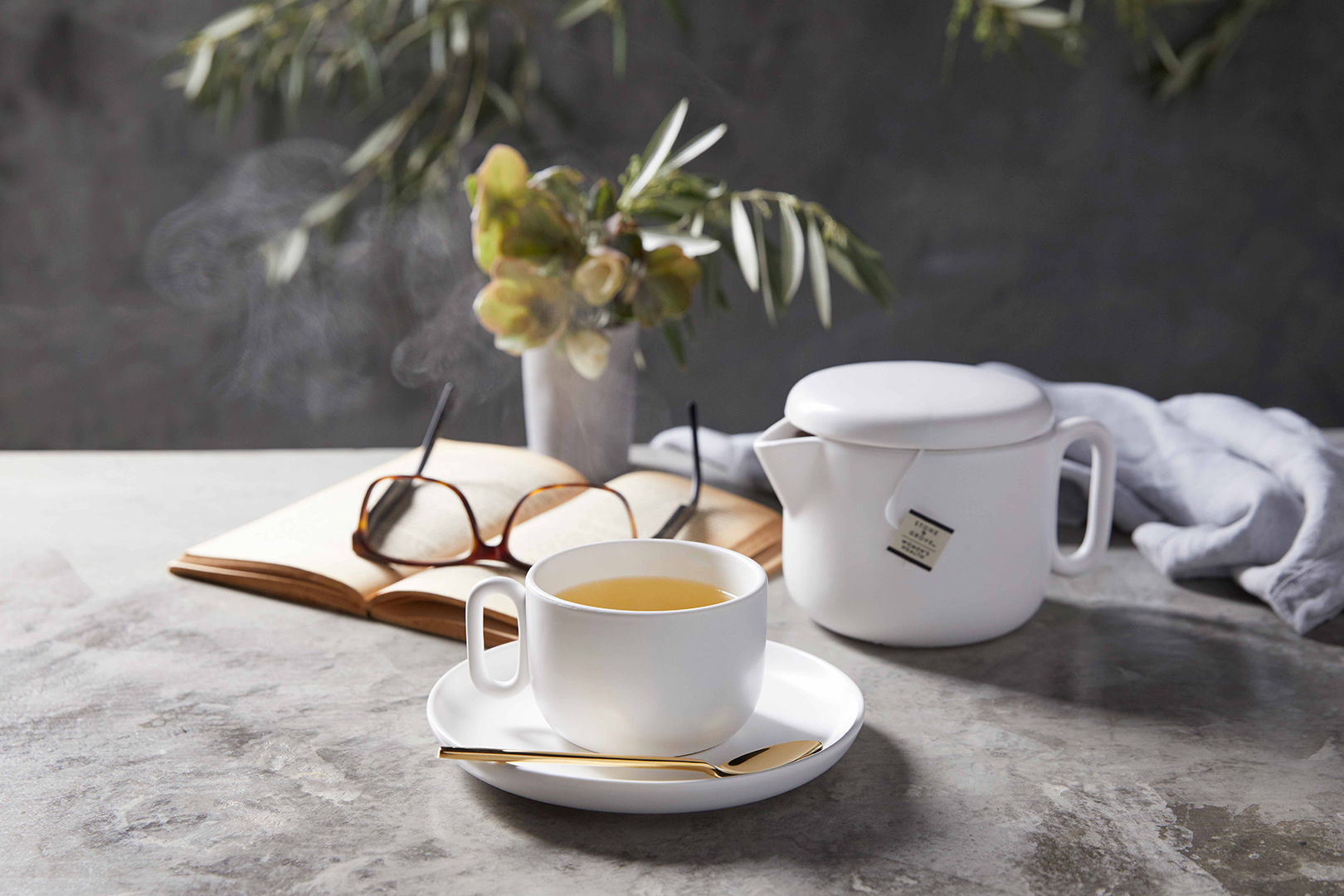A White tea cup with a gold spoon filled with steaming hot Women's Health night time hot tea on a grey background teapot and book with glasses